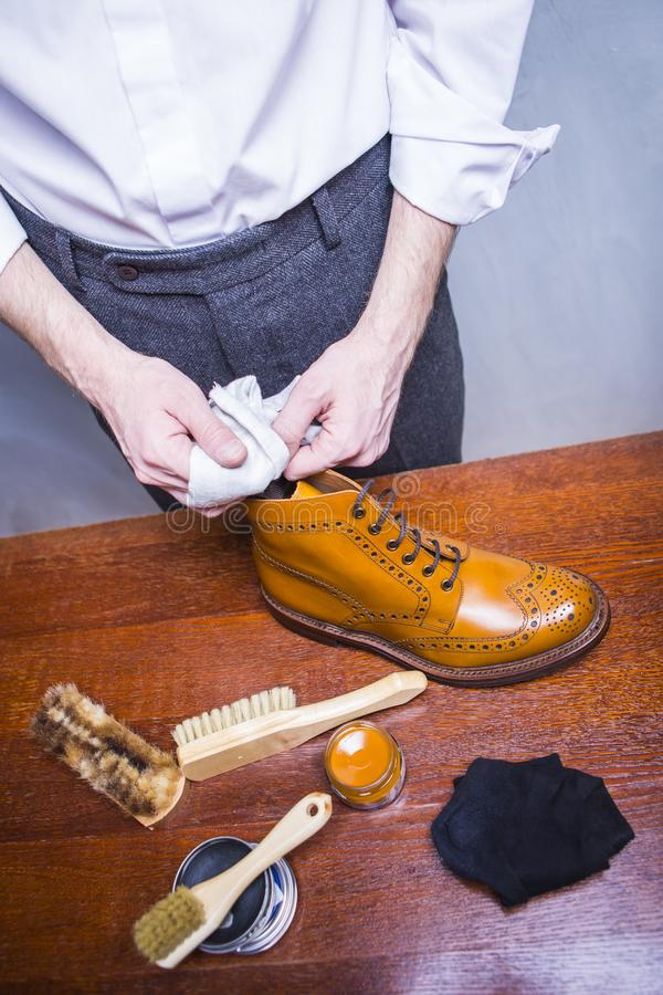 Limpiador de zapatos masculino que usa el paño suave para Tan Brogue Derby Boots masculina de pulido imágenes de archivo libres de regalías