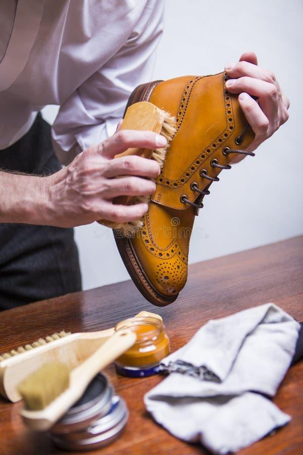 Limpiador de zapatos que usa el cepillo para Tan Brogues masculina de pulido fotos de archivo libres de regalías