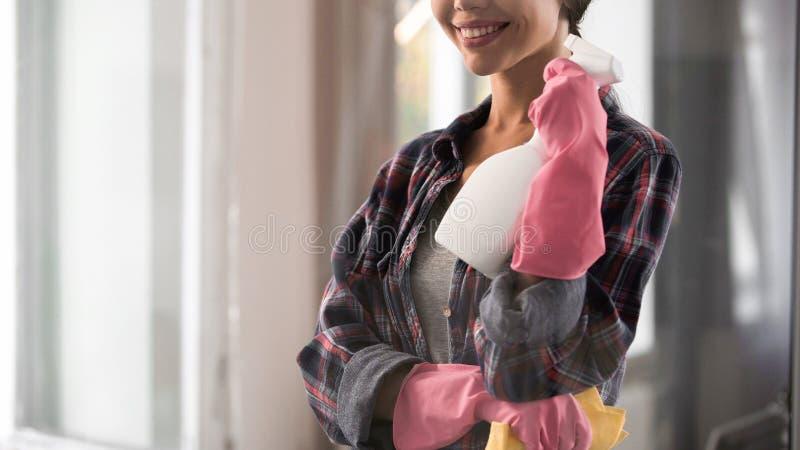 Limpiador femenino feliz que mira satisfecho el vidrio lavado brillante después del trabajo, pureza imagenes de archivo