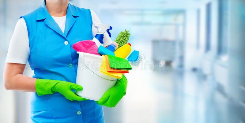 Limpiador femenino que sostiene un cubo con las fuentes de limpieza imagen de archivo libre de regalías