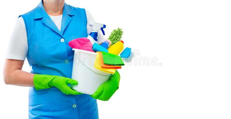 Limpiador femenino que sostiene un cubo con las fuentes de limpieza aislado imagen de archivo libre de regalías