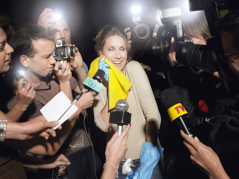 Limpiador femenino rodeado por los paparazzis fotos de archivo libres de regalías