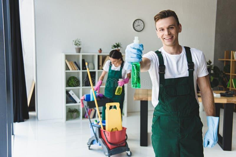 limpiador masculino joven en los guantes de goma que sostienen la botella del espray con detergente y la sonrisa fotos de archivo