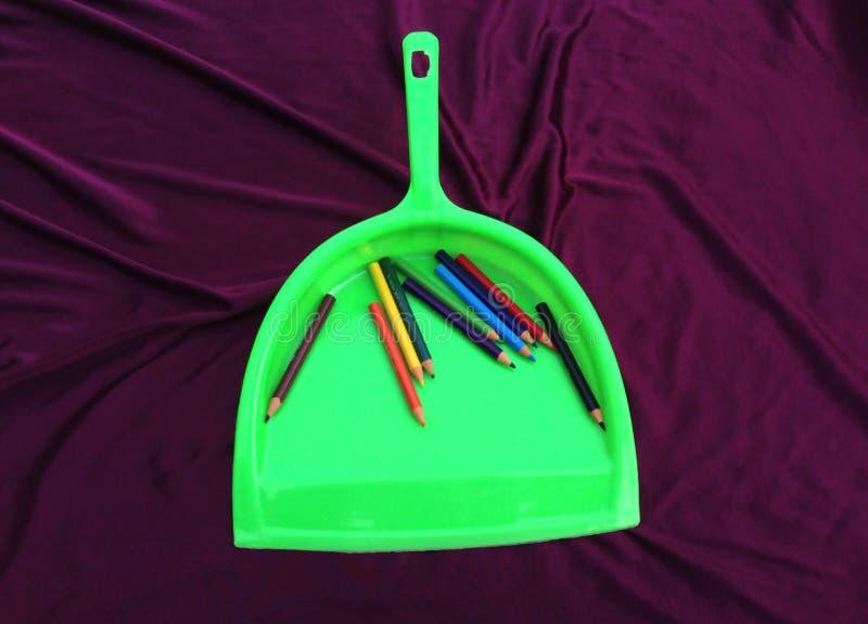 Limpiador verde de la basura con el lápiz aislado en fondo negro fotografía de archivo libre de regalías