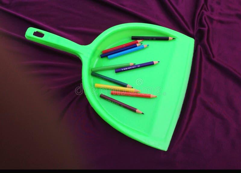 Limpiador verde de la basura con el lápiz aislado en fondo negro foto de archivo libre de regalías