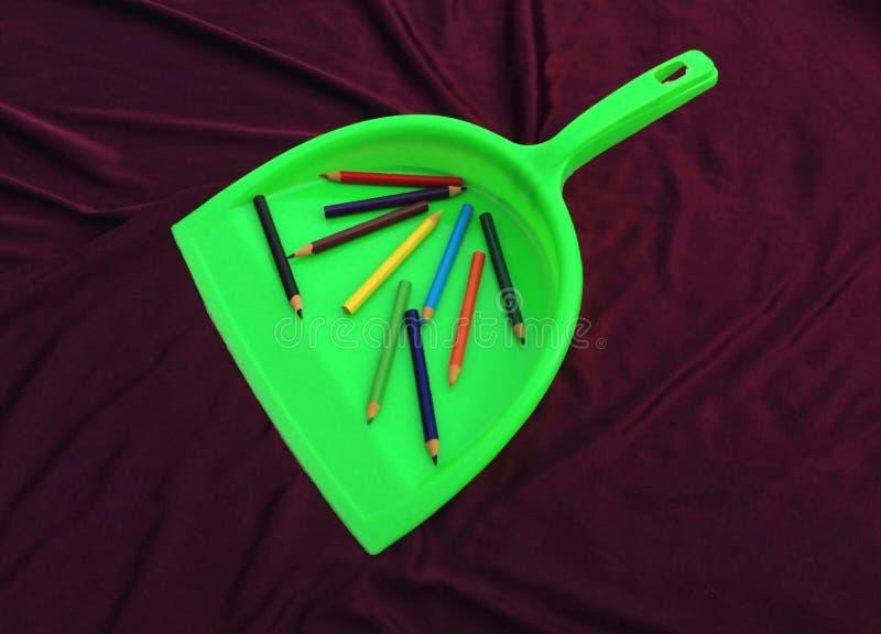 Limpiador verde de la basura con el lápiz aislado en fondo negro fotografía de archivo