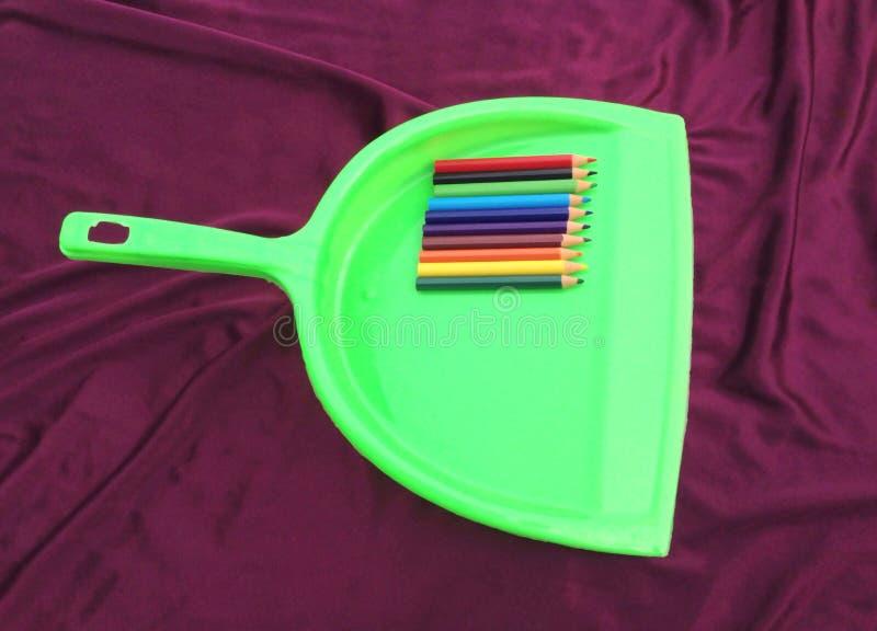 Limpiador verde de la basura con el lápiz aislado en fondo negro imágenes de archivo libres de regalías