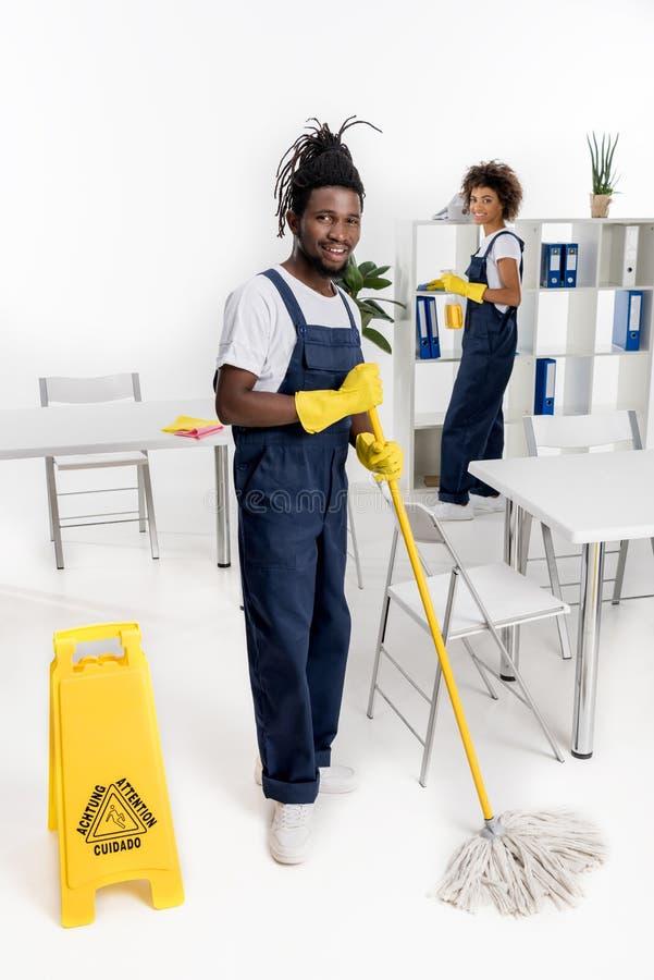 limpiadores afroamericanos sonrientes jovenes con el equipo de la limpieza fotos de archivo