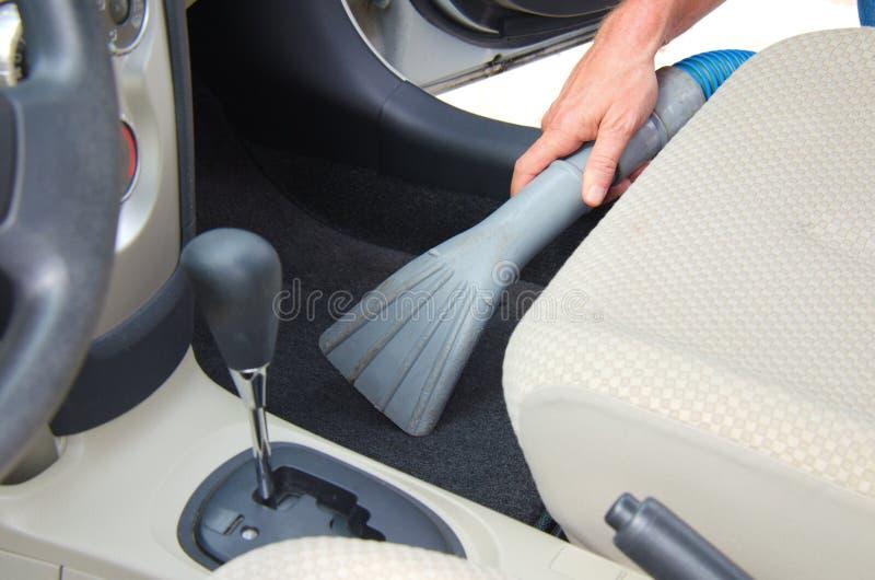 Limpiar un detalle interior del automóvil con la aspiradora del coche fotografía de archivo