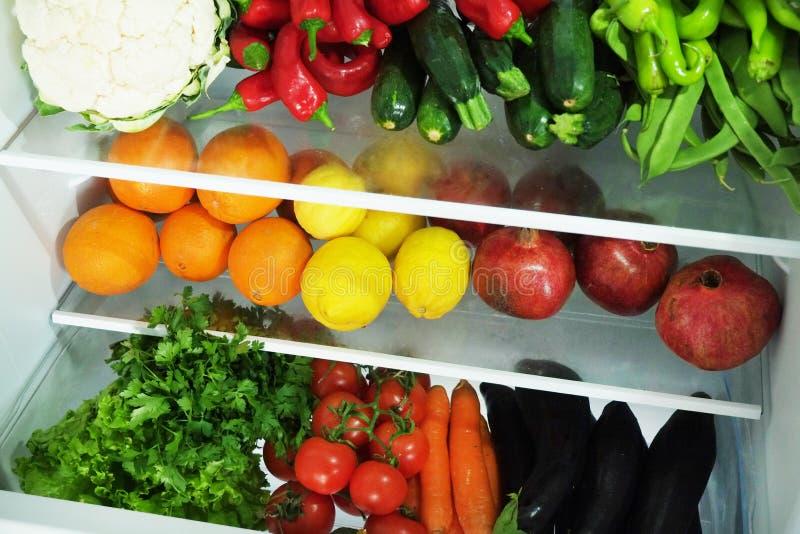 Limpie diversa mezcla de la verdura y de la fruta estacada en los estantes del refrigerador abierto Luz del día, productos orgáni imagenes de archivo