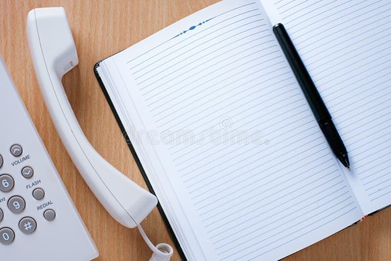 Limpie el cuaderno, la pluma y el teléfono en el escritorio fotografía de archivo libre de regalías