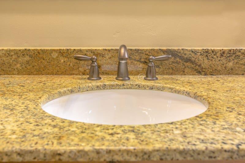 Limpie el fregadero del granito en cuarto de baño del hogar modelo fotos de archivo