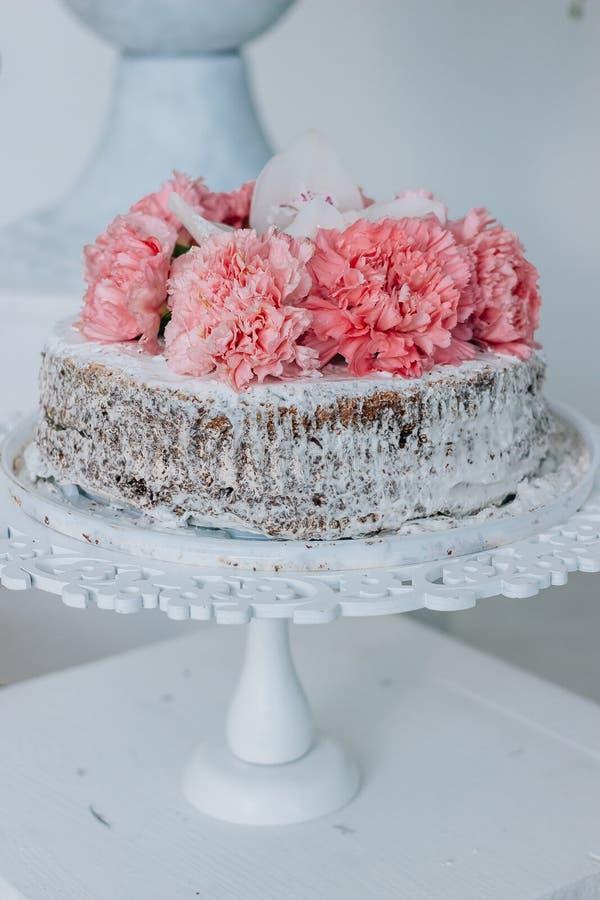 Limpie el pastel de bodas con esponja adornado con las flores en un pedestal blanco fotografía de archivo