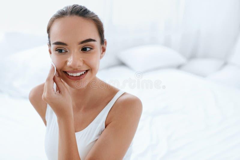 Limpie la cara Piel de limpieza de la mujer hermosa con el cojín cosmético imágenes de archivo libres de regalías