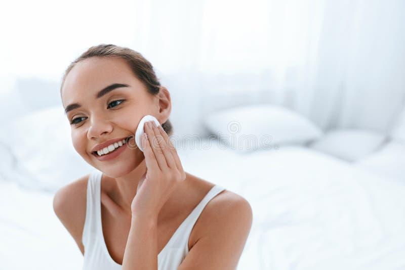 Limpie la cara Piel de limpieza de la mujer hermosa con el cojín cosmético fotos de archivo