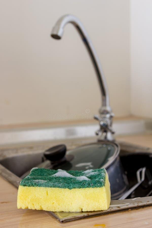 Limpie la esponja y el artículos de cocina en fregadero imagen de archivo