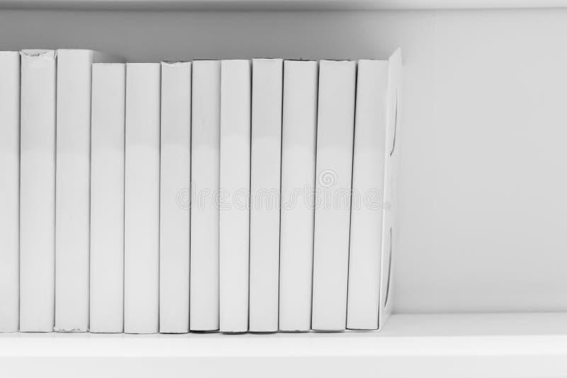 Limpie la lectura ordenada blanca del hogar del estante de librería fotos de archivo