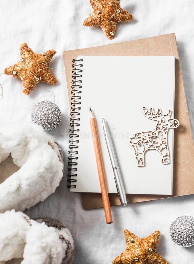 Limpie la libreta en blanco, ornamentos de la Navidad, reno de madera, juguetes, botas caseras del ugg en un fondo ligero, visión imágenes de archivo libres de regalías