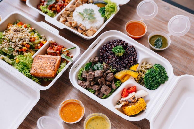Limpie las cajas de la comida de la comida: arroz y baya del arroz con carne de vaca, los salmones y el pollo en diversas verdura fotografía de archivo