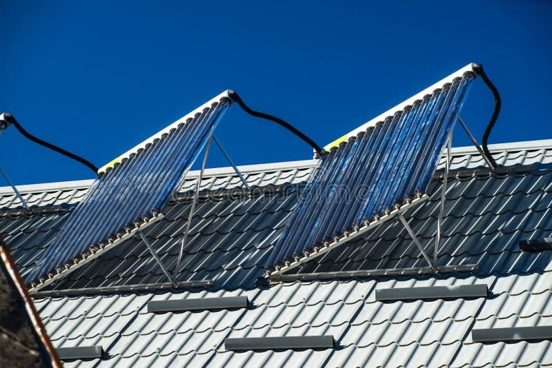Limpie los colectores con la aspiradora solares en el tejado D?a asoleado imágenes de archivo libres de regalías