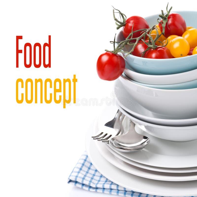 limpie los cuencos, las placas y los tomates de cereza clasificados, primer foto de archivo