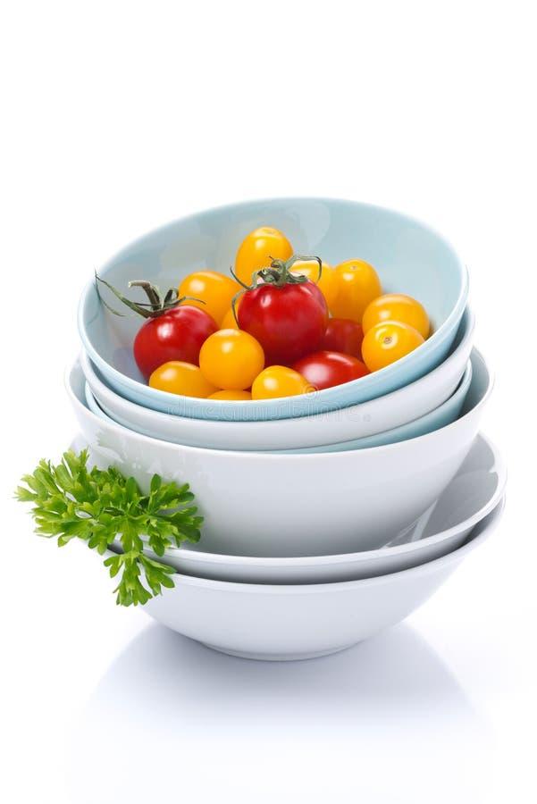 Limpie los cuencos, tomates de cereza clasificados y perejil, aislados imagenes de archivo