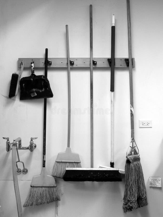 Limpieza comercial: escobas, recogedor de polvo y fregona imagen de archivo