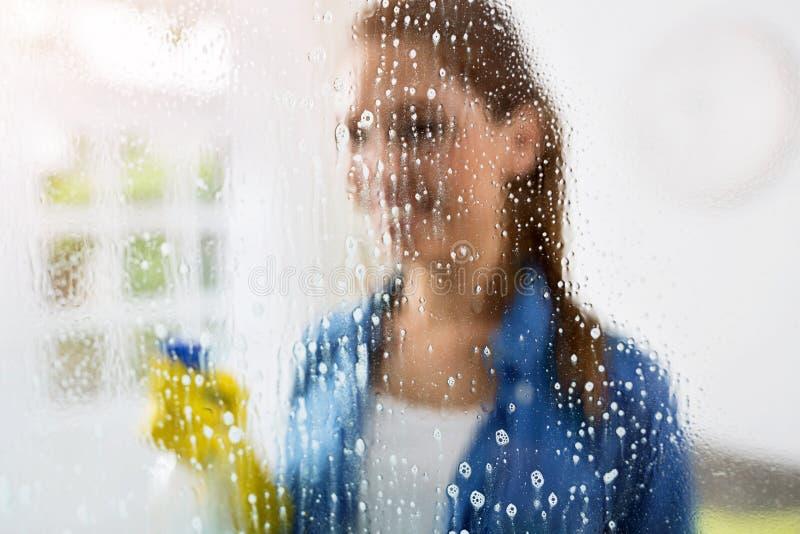 Limpieza - cristal de ventana de la limpieza con el detergente imagen de archivo