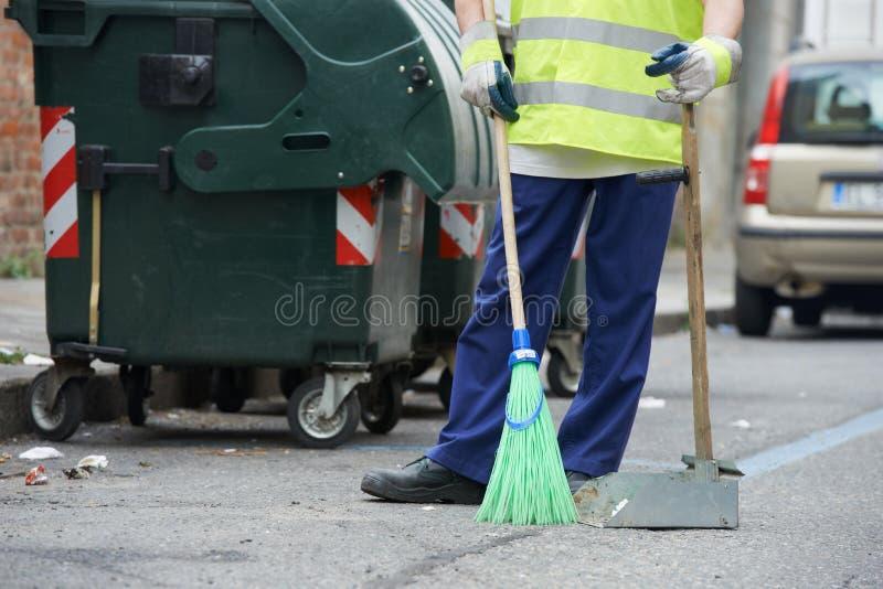 Limpieza de la calle y el barrer con la escoba foto de archivo