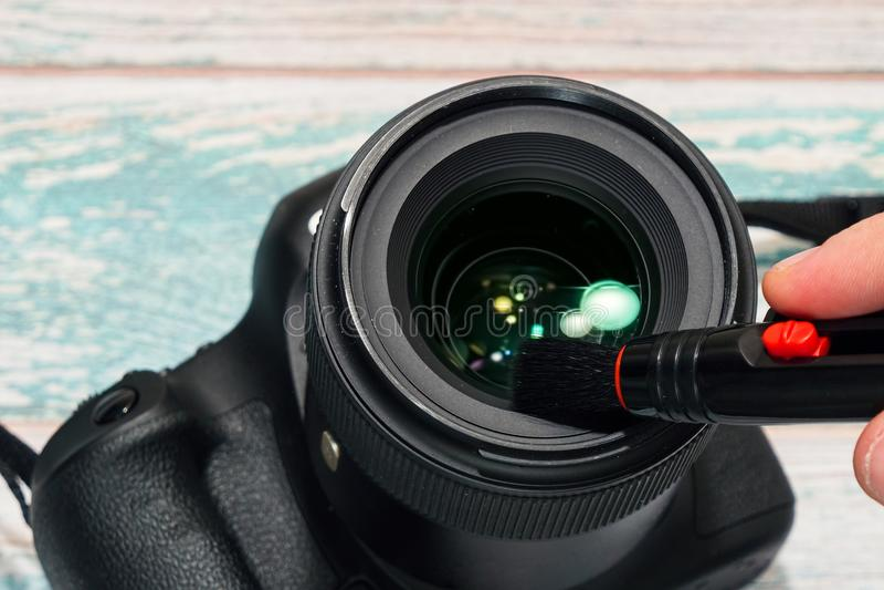 Limpieza de la lente de cámara de Digitaces SLR foto de archivo libre de regalías