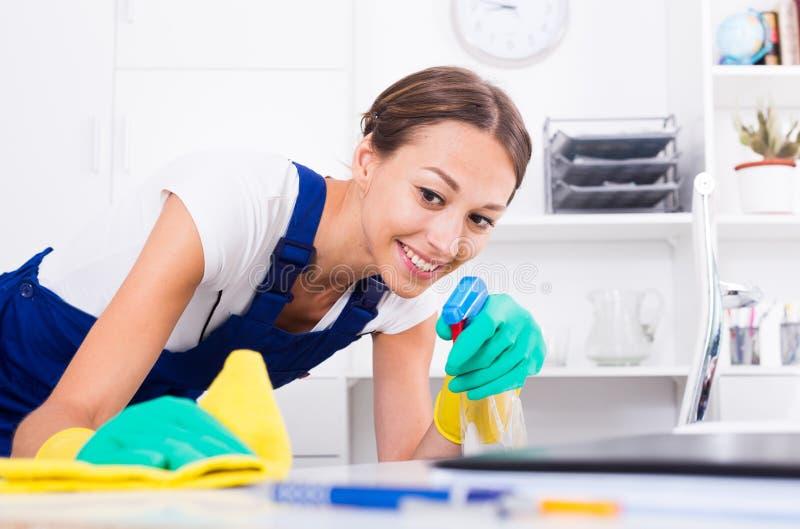 Limpieza de la mujer en oficina de la compañía imagen de archivo