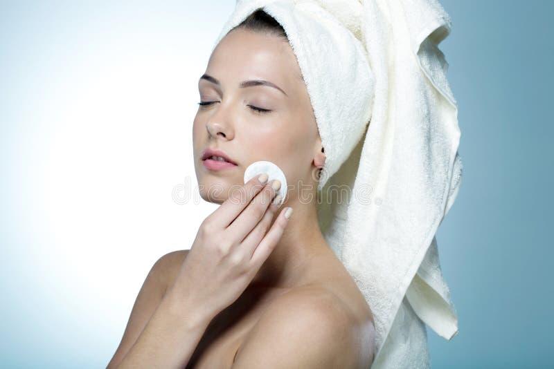 Limpieza de la mujer su cara foto de archivo libre de regalías