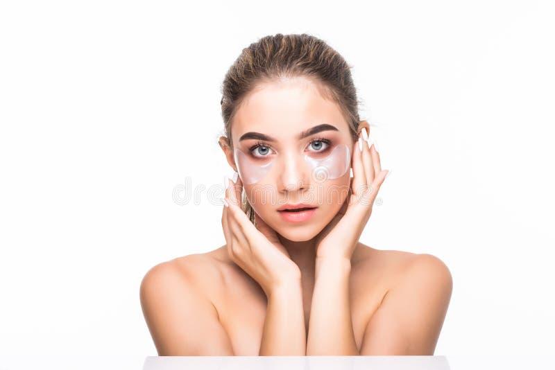 Limpieza de la mujer su cara La mujer joven hermosa con aclara remiendos o el yeso en su nariz que mira la cámara Concepto del cu foto de archivo