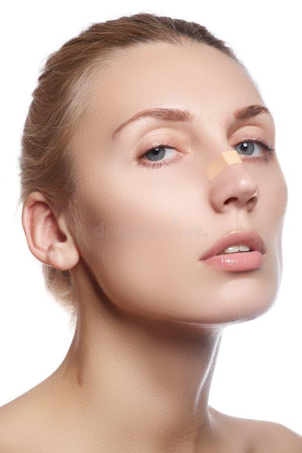 Limpieza de la mujer su cara La mujer joven hermosa con aclara remiendos o el yeso en su nariz que mira la cámara Concepto del cu fotografía de archivo libre de regalías