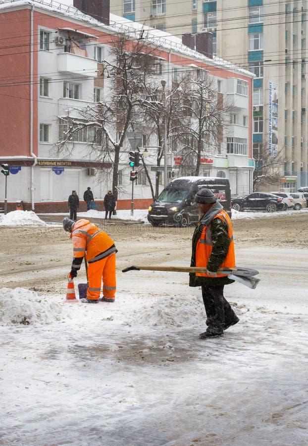 Limpieza de la nieve de los trabajadores de los servicios de la ciudad en la ciudad de Belgorod de Rusia fotos de archivo libres de regalías
