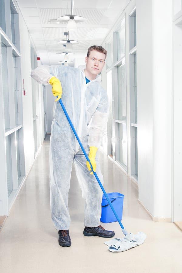 Limpieza de la oficina en guardapolvos imagen de archivo