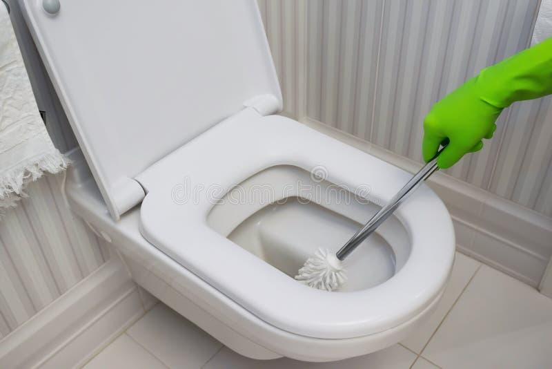 Limpieza de la taza del inodoro limpiador en guantes de goma verdes imagen de archivo