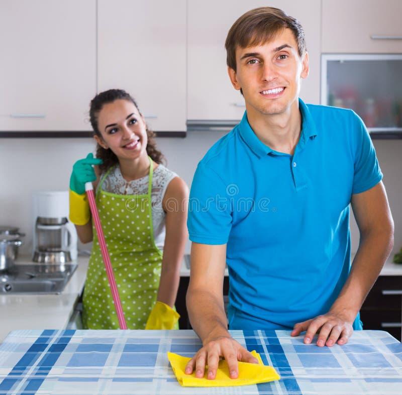 Limpieza de los pares de la familia en la cocina junto y la sonrisa imágenes de archivo libres de regalías