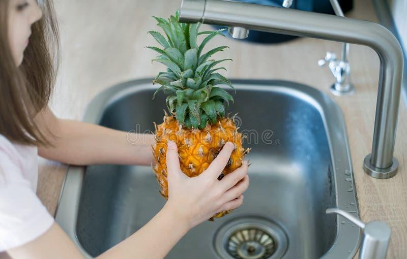 Limpieza de piña y lavado en un lavabo de cocina Lavar alimentos Manos de niño sujetando una apetitosa piña fresca Estilo de vida fotos de archivo libres de regalías