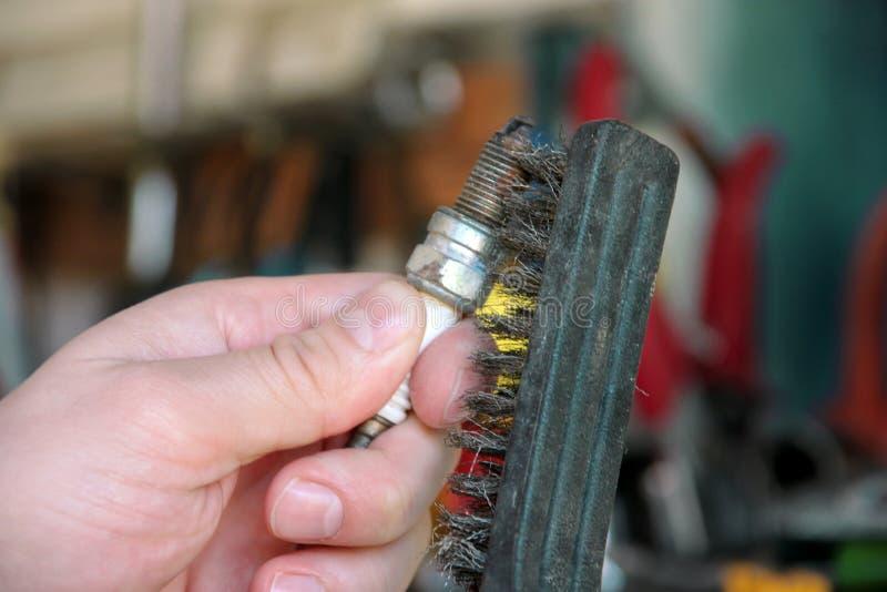Limpieza de una bujía del motor de coche con el cepillo de alambre en garaje del coche El mecánico está cepillando la bujía usada fotos de archivo libres de regalías