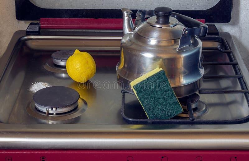 Limpieza de una estufa de gas con bicarbonato y el limón de sosa foto de archivo