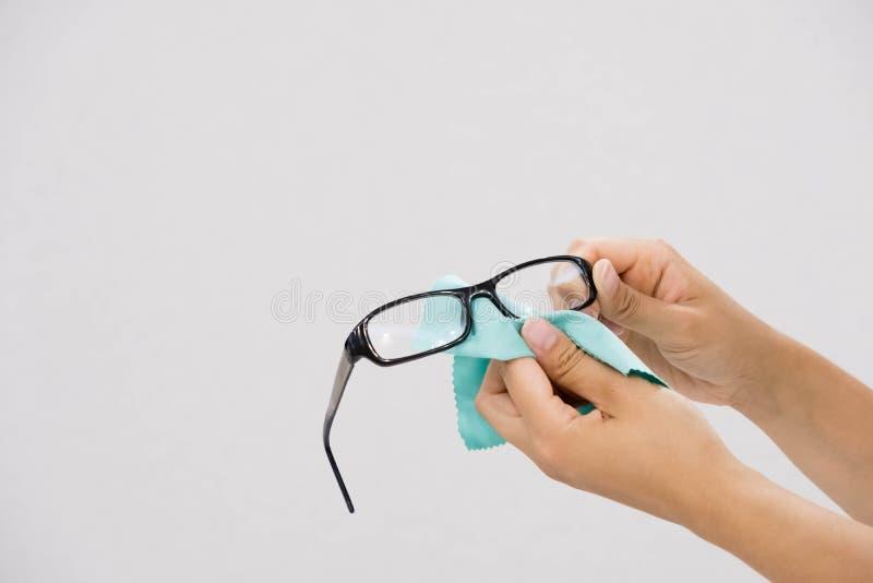 Limpieza de vidrios con el paño fino de la microfibra Lente de limpieza de los vidrios de la mano de las mujeres con el fondo del foto de archivo