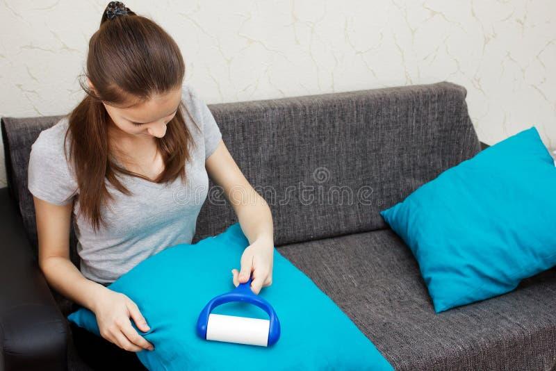 Limpieza del apartamento La muchacha europea joven limpia la almohada en casa fotos de archivo