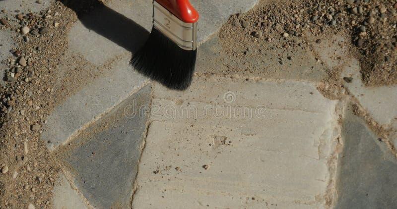Limpieza del arqueólogo con el piso de mosaico antiguo del cepillo imagenes de archivo