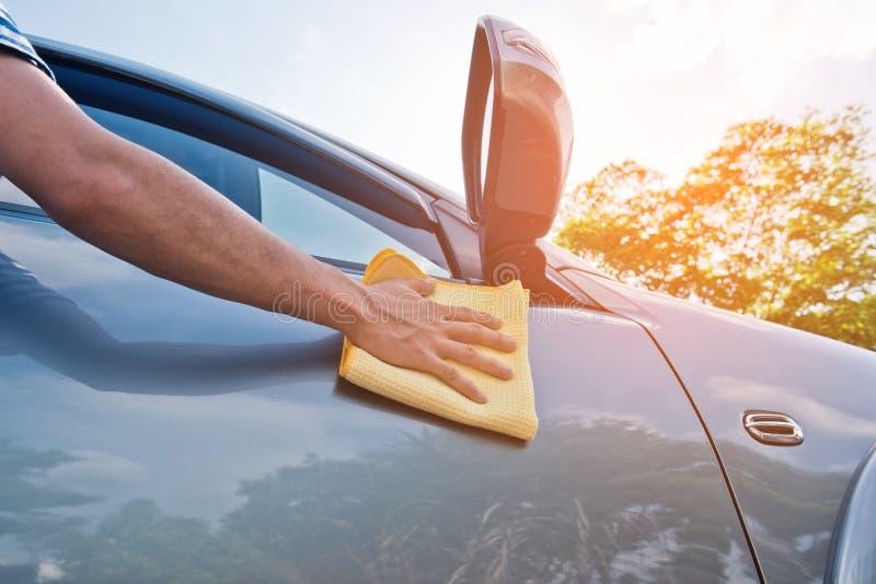 Limpieza del coche con la capa del paño y de la cera de la microfibra, tono del color del vintage imagenes de archivo