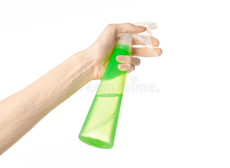 Limpieza del tema de la casa y del limpiador: la mano del hombre que sostiene una botella verde del espray para limpiar aislada e imagenes de archivo