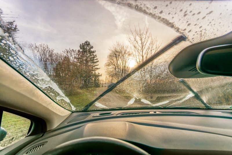 Limpieza del vidrio con los limpiadores del anticongelante y de parabrisas para una visión clara fotos de archivo libres de regalías