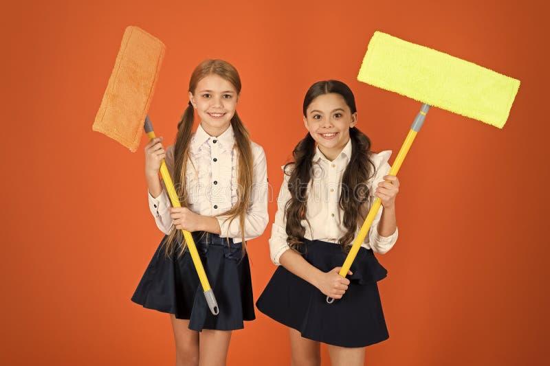 Limpieza estupenda del duper Colegialas lindas que sostienen las fregonas del piso Alumnos con las herramientas de limpieza Las n foto de archivo libre de regalías