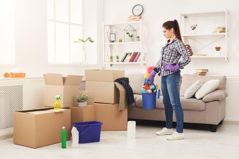Limpieza femenina joven su nuevo apartamento después de mover imagen de archivo