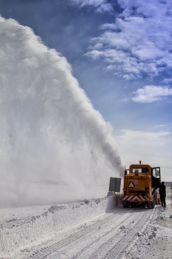 Limpieza nevada del camino por la máquina de la retirada de la nieve imagenes de archivo